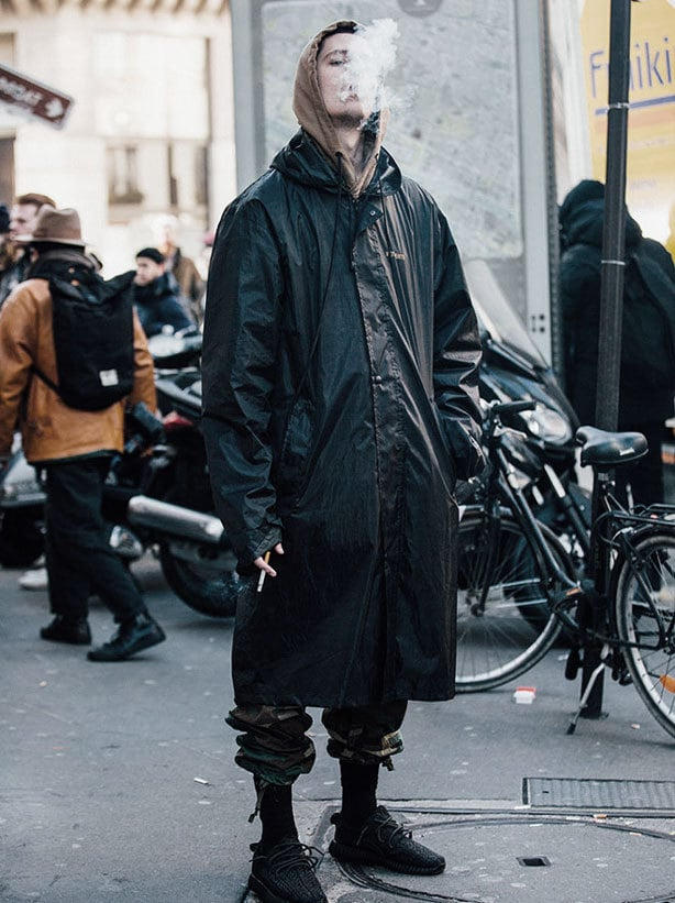 A man smokes a cigarette, wearing an oversized coat, layered urban fashion and baggy trousers