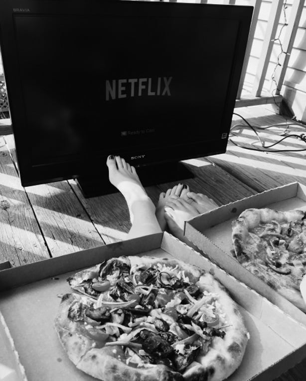 Black and white photo of a couple watching Netflix on TV, to represent  the term netflix and chill
