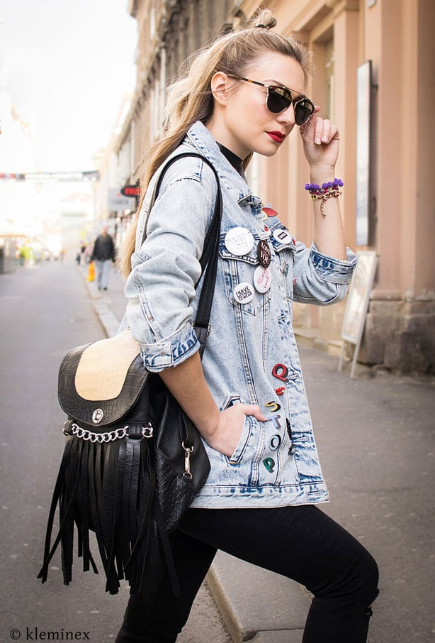A blonde woman wears a light denim jacket styled with patches and badges