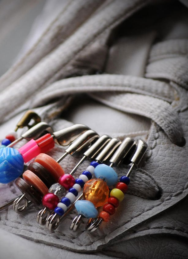 A close-up image of safety-pins being used to decorate a pair of shoes