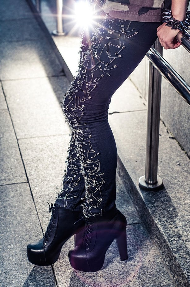 A picture of black skinny jeans decorated with lots of silver safety-pins