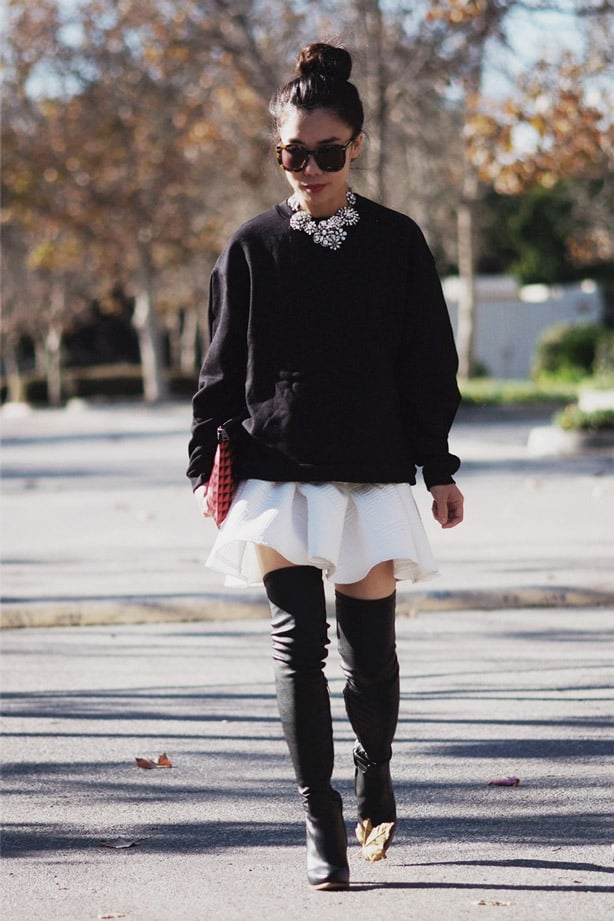 A woman walks down the street, wearing a black sweater, white mini skirt and black over-the-knee boots