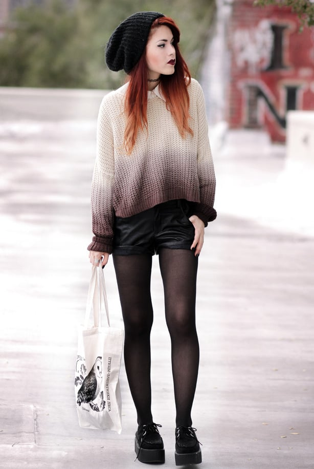 A woman wears a chunky knit ombre sweater, with shorts and black creepers for a messy winter punk style