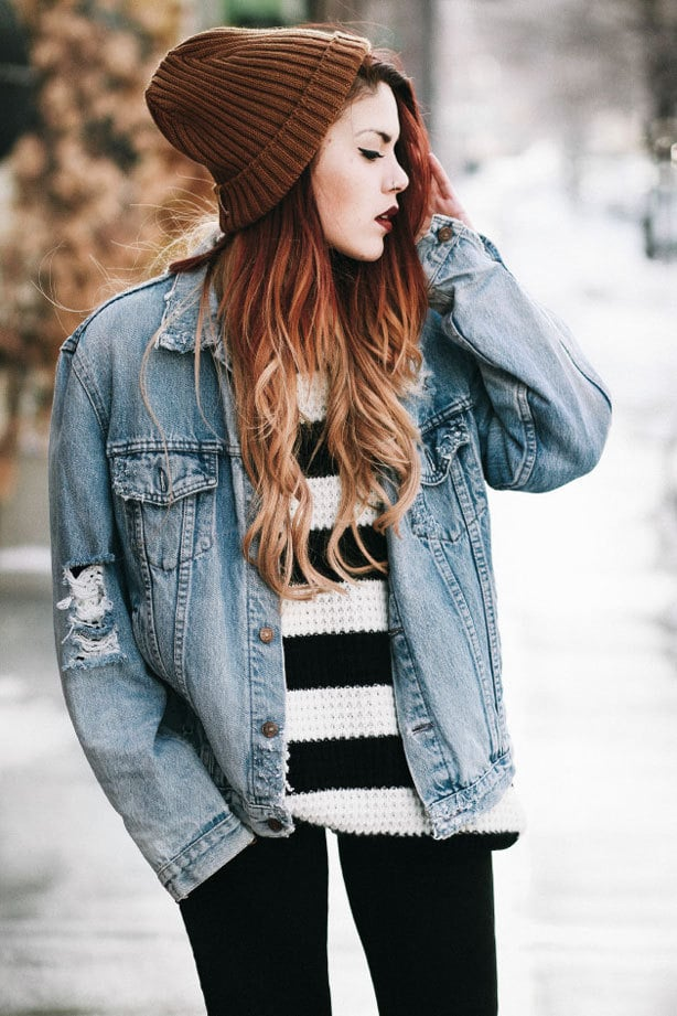 A red-haired woman wearing a winter punk outfit with a woolly hat, blue denim jacket and a chunky knit sweater
