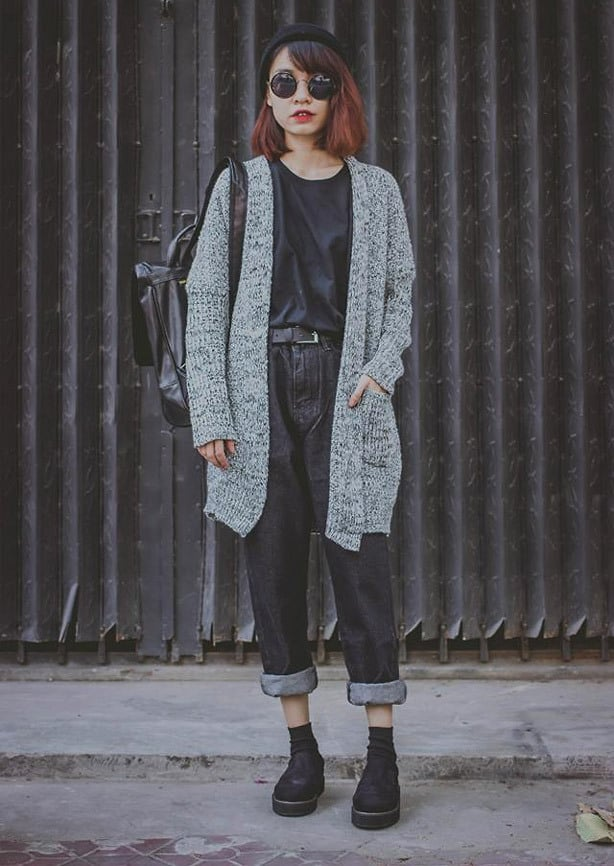 A picture of a woman wearing punk- style winter clothing with an oversized wool cardigan, black t-shirt and upturned black jeans