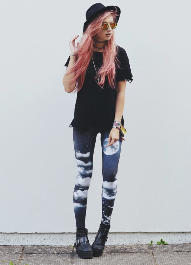 A young, pink-haired woman wearing night sky printed leggings, a black tee shirt and fedora hat