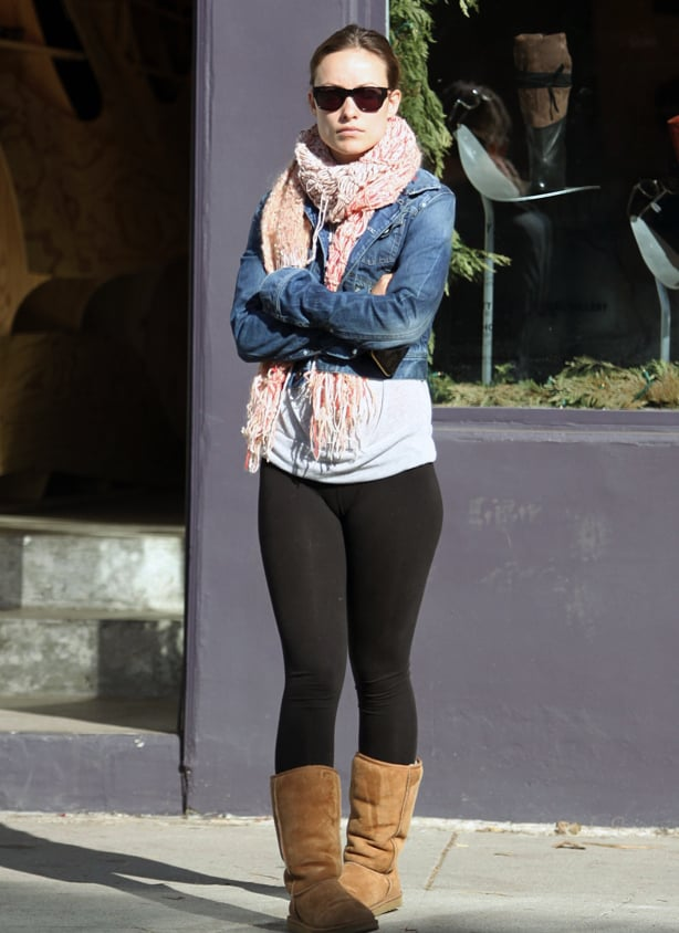 A woman wearing a chunky scarf, denim jacket, thick black leggings and tan coloured Ugg style boots