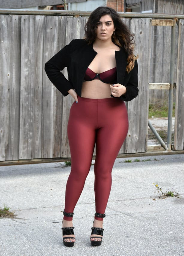 A plus-sized model wearing platform sandals, ruby red Lycra leggings, a black cropped jacket and red bra underneath