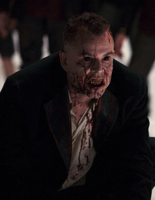 A still from the underrated horror movie 30 Days of Night, showing a vampire with black eyes and bloody teeth