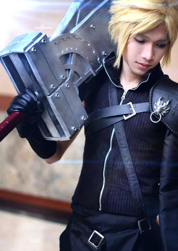 Close up of a man dressed as Cloud from Final fantasy, wearing video game inspired fashion, a black sweater and leather gloves