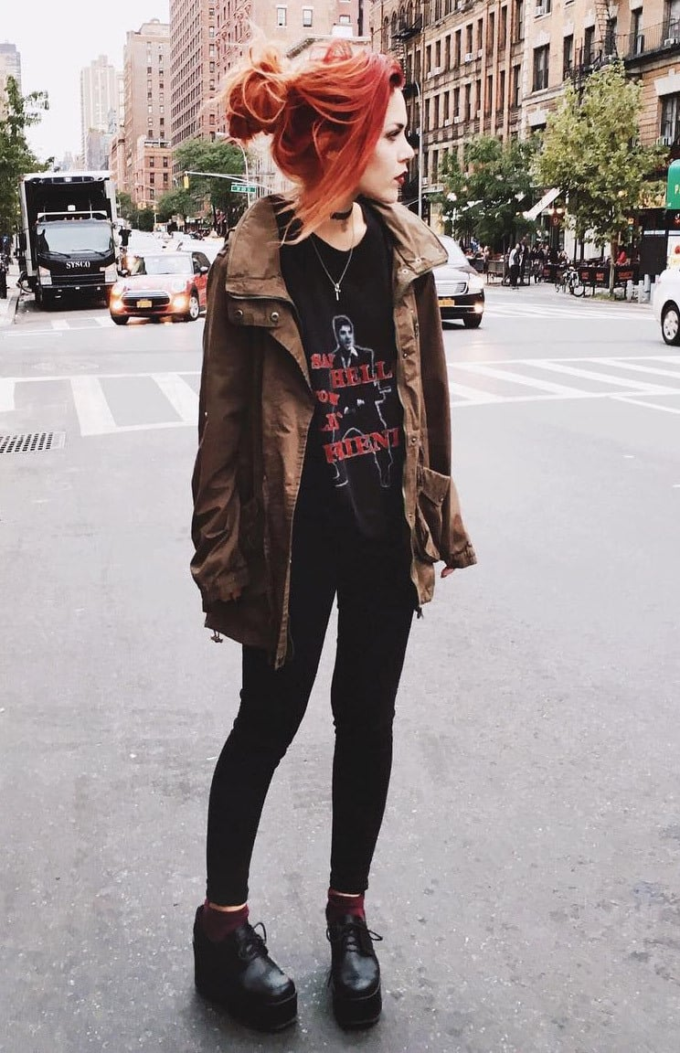 Red haired girl wearing a grunge outfit, platform boots and a trenchcoat