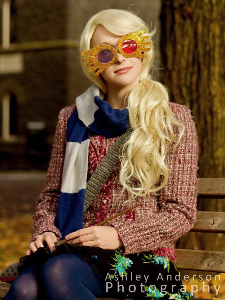 A girl wearing a blonde wig, funky colored glasses and knitted sweater with a blue and white striped scarf