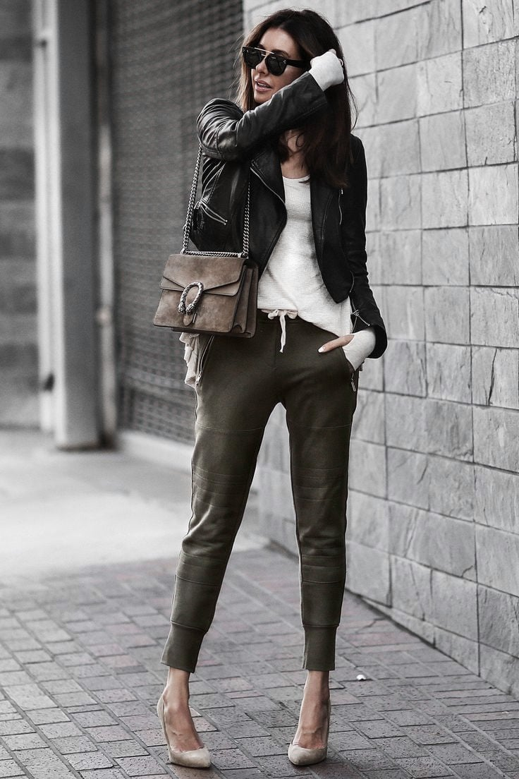A woman wearing a casual date night outfit, with khaki pants, a black leather jacket and a suede handbag