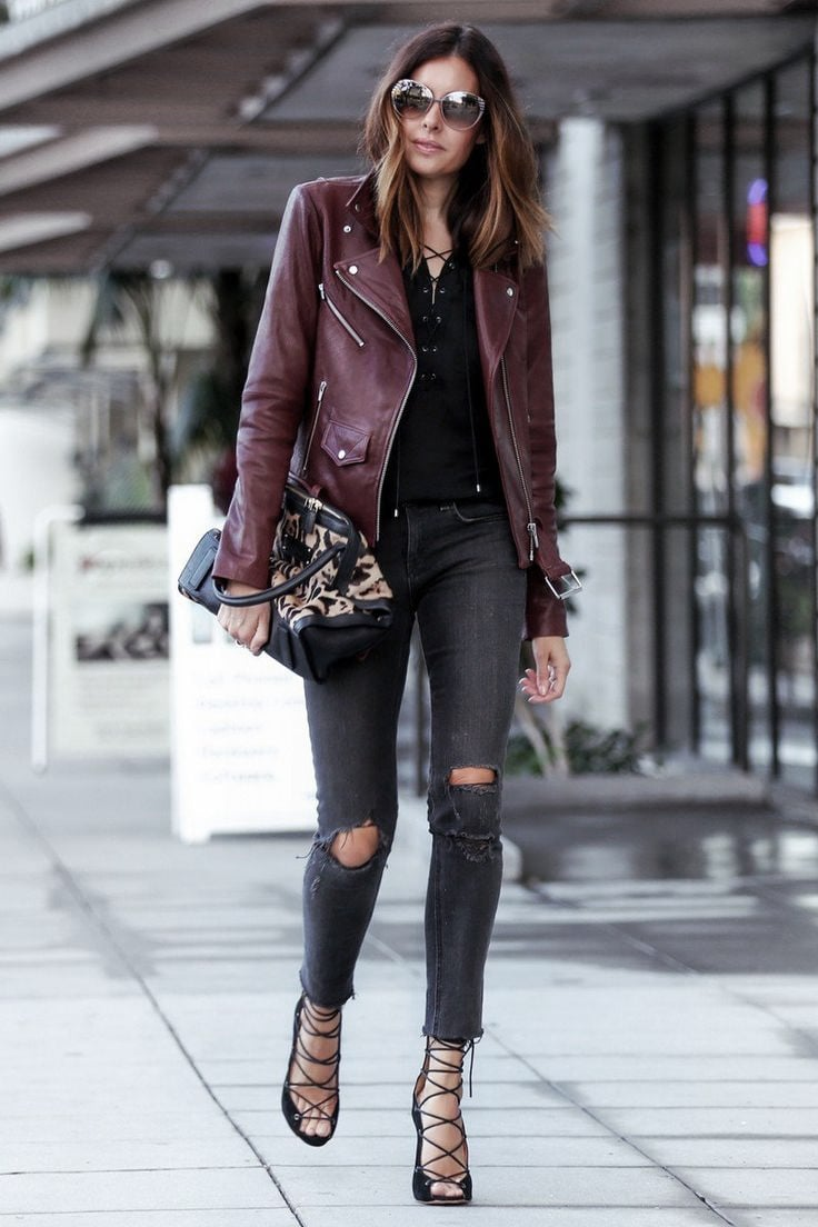 A woman walks through the street, wearing a burgundy leather jacket, ripped black jeans, spaghetti strap sandals and holds a cute handbag