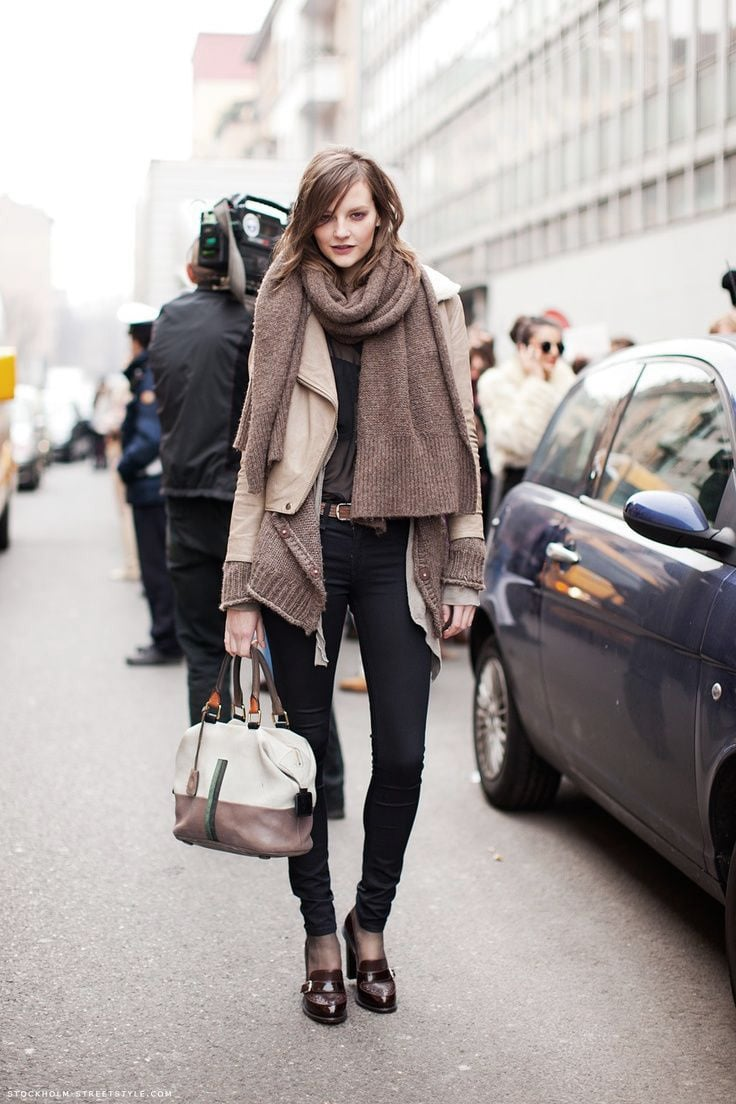A woman wears an oversized knitted scarf, a brown coat, skinny jeans and brown shoes as part of a winter fashion ensemble