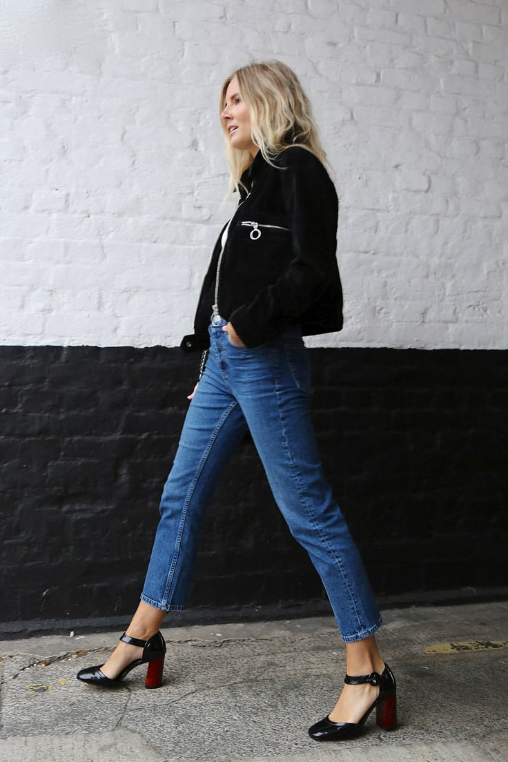 A blonde model wears straight leg jeans, mary-janes and a black blazer
