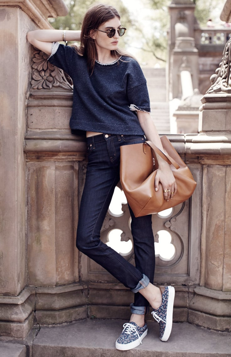 A woman wears high waisted jeans with a blue sweater and sneakers