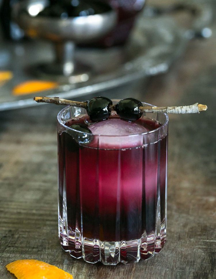 Red moon over manhattan cocktail with ice and cherries in a tumbler