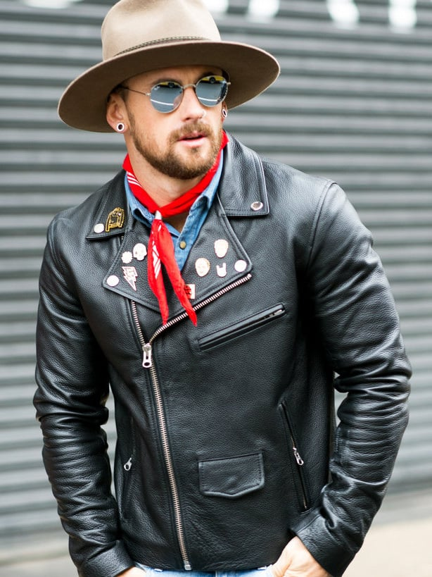 A man wearing a leather jacket with badges pinned to the front, a red neckerchief and sunglasses