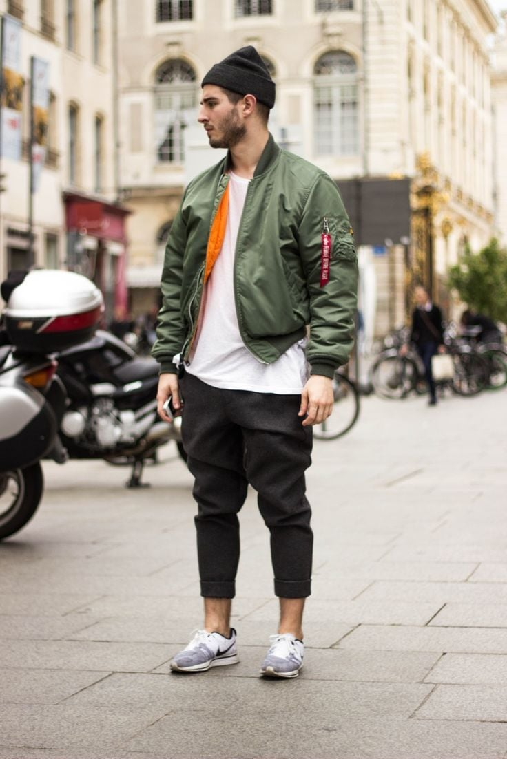 A man wearing a green bomber jacket with cropped trousers and a headband for a warm winter outfit
