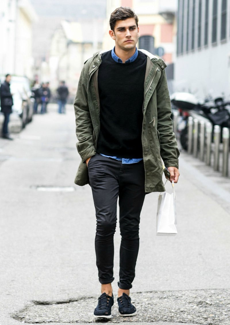 A man wears an olive drab utility jacket and a black sweater with dark jeans for a winter ensemble