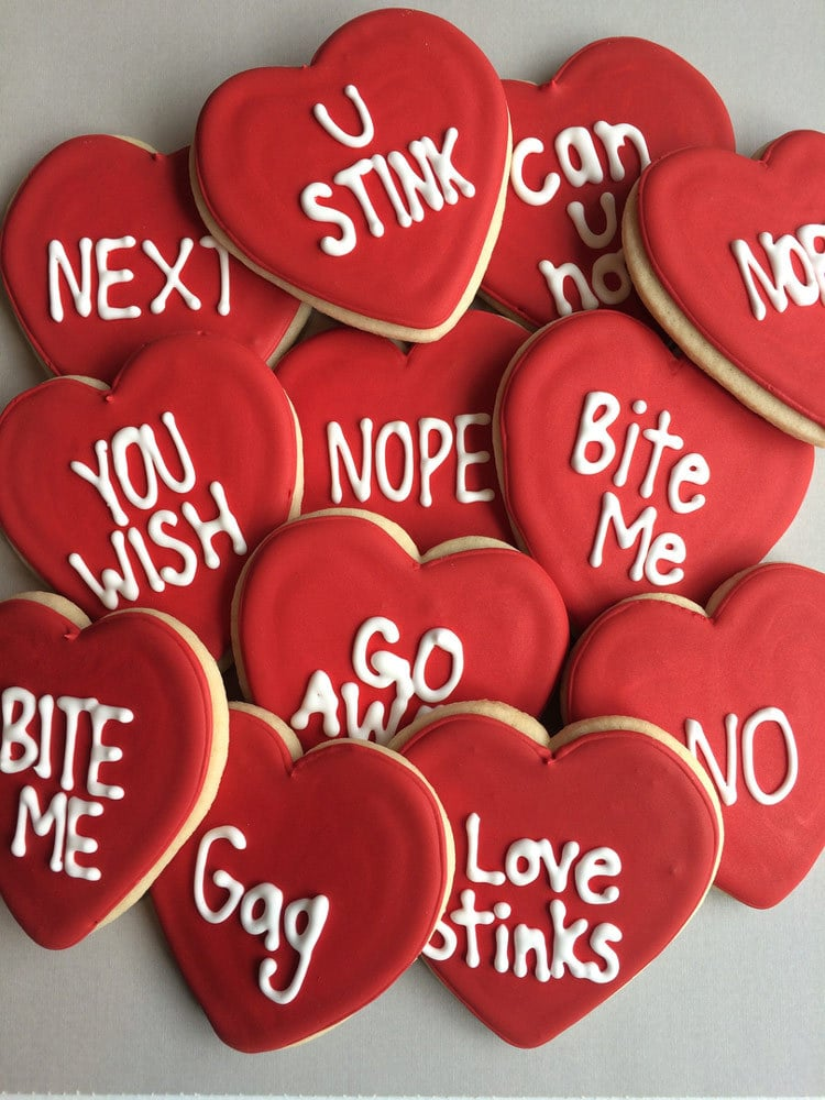 Heart-shaped Anti Valentines cookies, with insults written on in icing