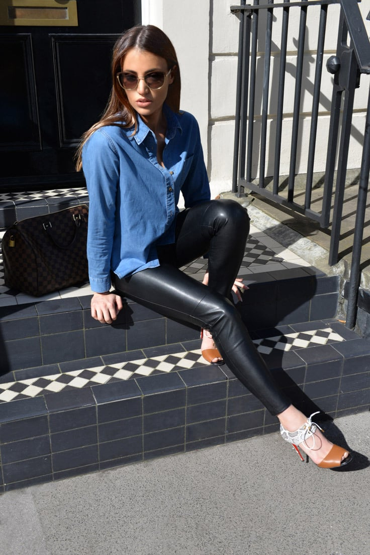 A model wears sunglasses, a blue denim shirt and leather leggings