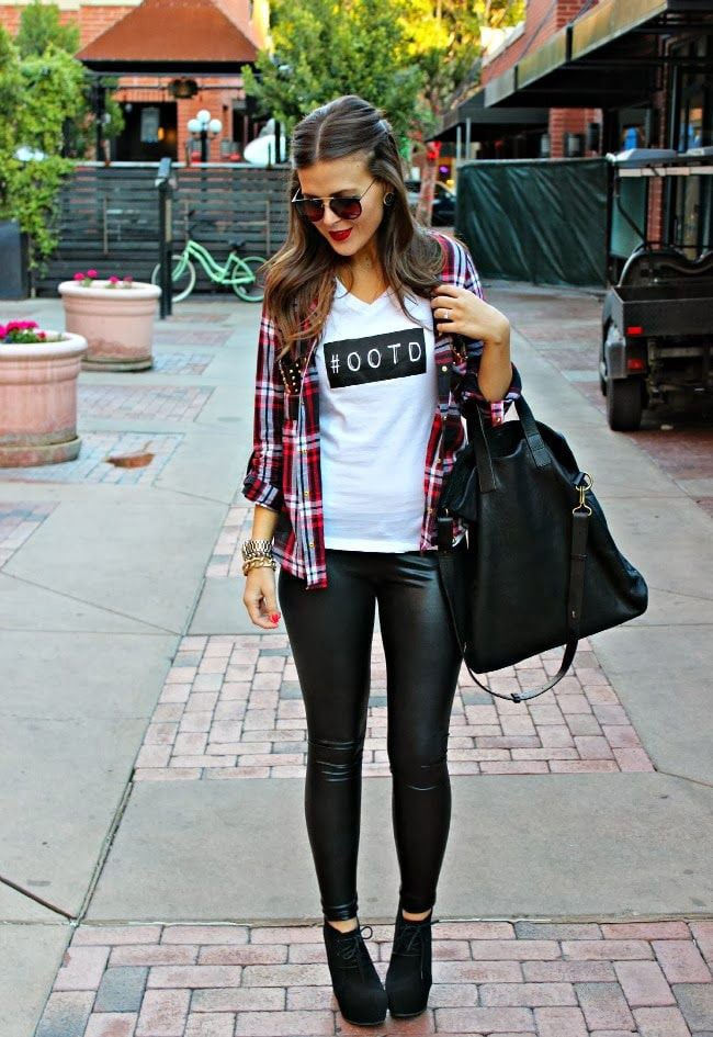 A girl wearing an open checked shirt, a slogan t-shirt and leather-look leggings as part of a street casual style