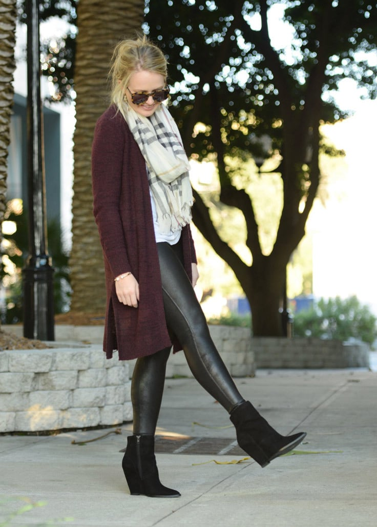 A blonde woman wears a knitted scarf and cardigan with some black lether leggings and boots