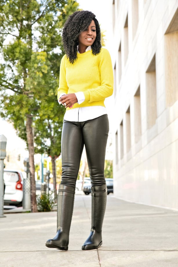 A model wears a mustard yellow sweater and chirt paired with leather leggings for an office casual outfit