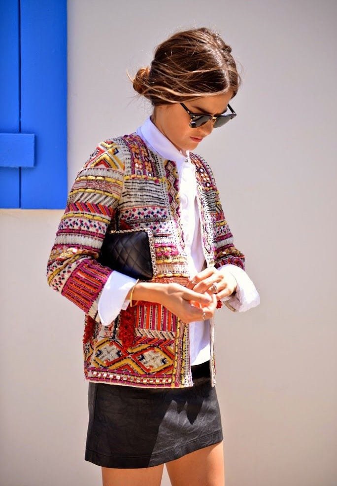 A woman wears an intricate boho jacket embroidered with bright oranges, reds and yellows