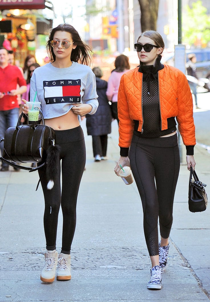 Two women walk down the street wearing athleisure outfits with bomber jackets, leggings and sneakers in bright colors