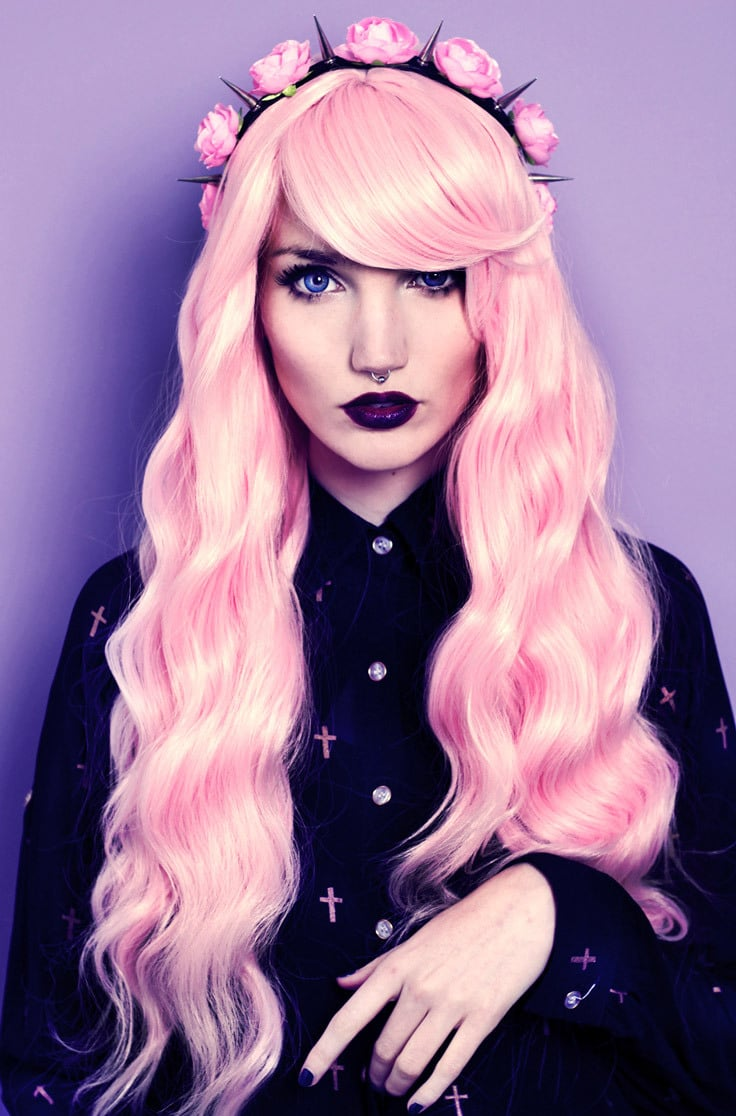 A pastel goth portrait of a woman with pastel pink hair, septum piercing and pastel gothic makeup