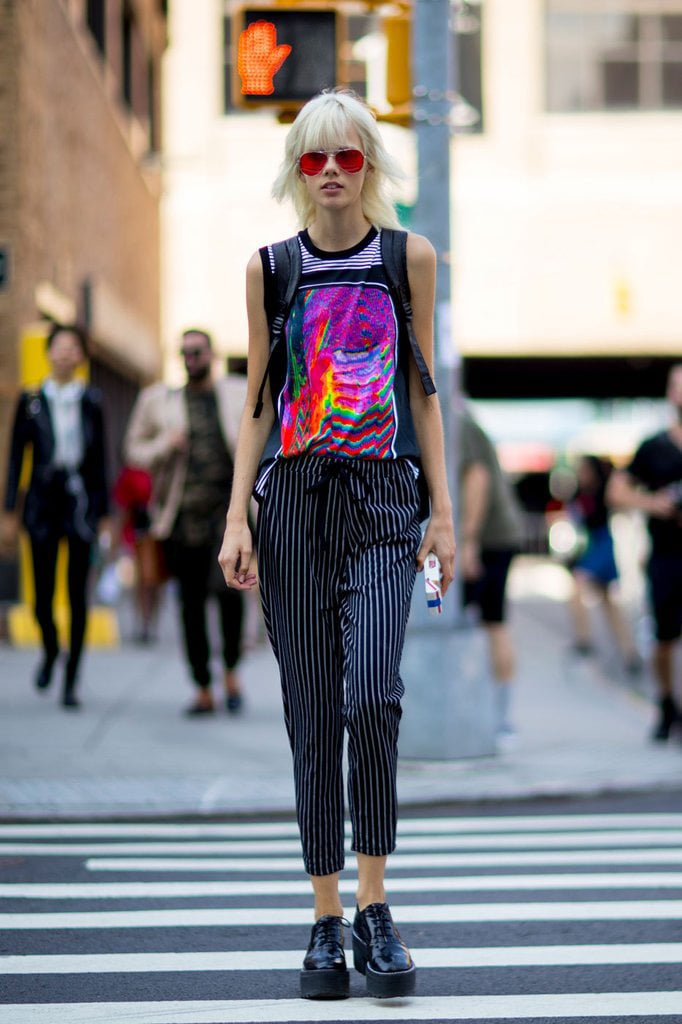 A bleach blonde woman wearing a preppy streetwear outfit with pinstripe trousers, a graphic tank top and platforms