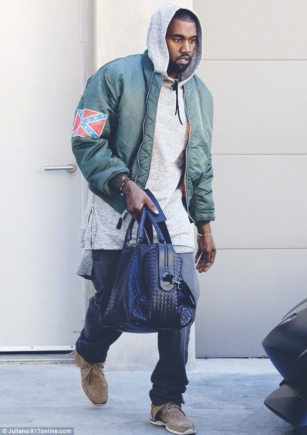 Kanye West wears a grey hoodie underneath a green bomber jacket as part of an urban style