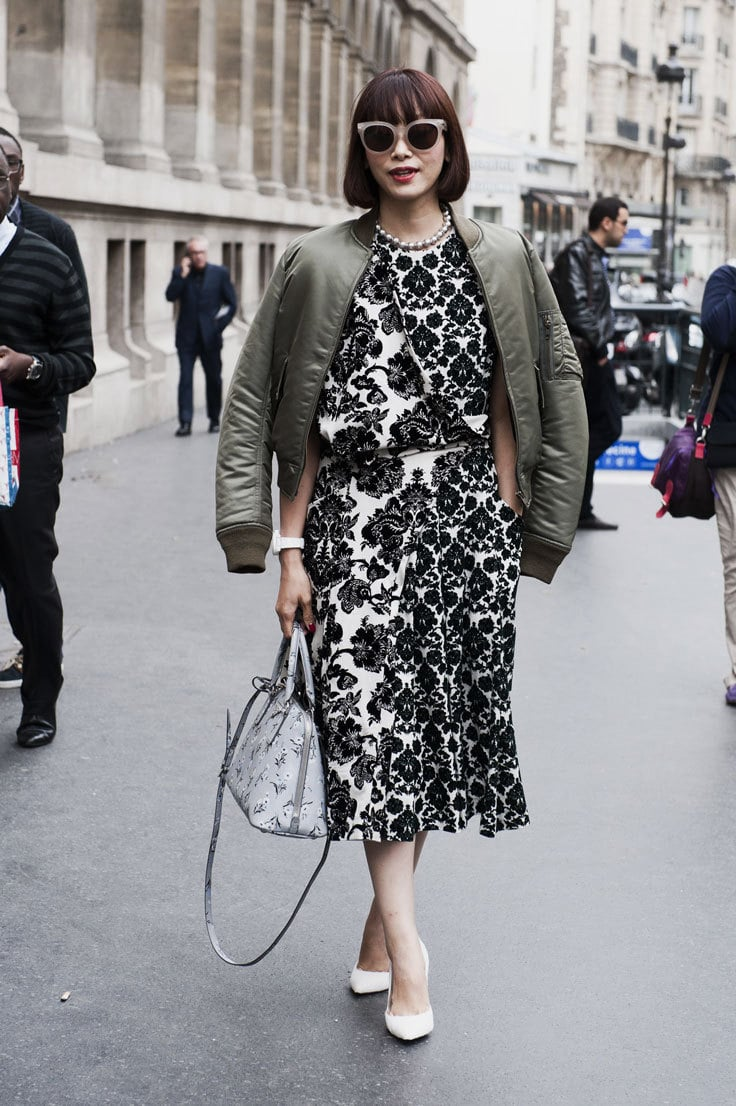 A woman wears a black and white floral dress layered with a green bomber jacket