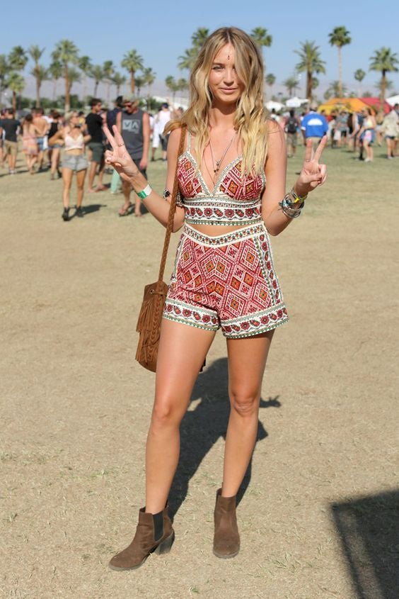 A blonde woman give the peace sign wearing a matching two-piece tank and shorts in aztec patterns, perfect for alternative festival fashion