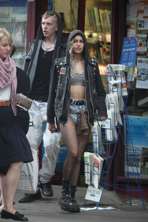 Super edgy sleaze punk fashion from Alice Dellal, wearing a cutoff leather jacket, denim shorts, ripped fishnets and grungy combat boots