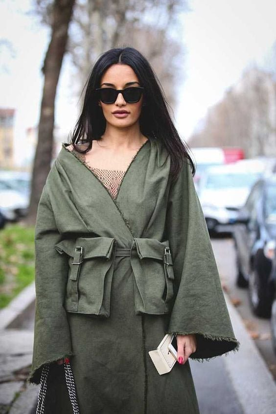 A brnette model wears a long khaki overcoat with oversized pockets