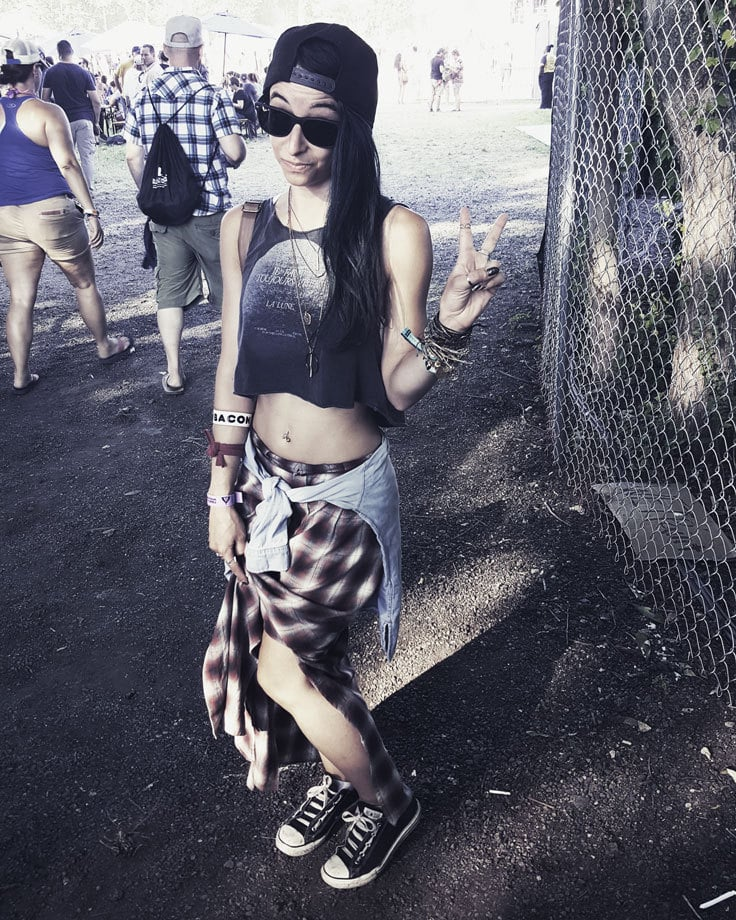 Alternative festival outfit with a vintage band tee, plaid shirt and denim shorts for a vintage rock style