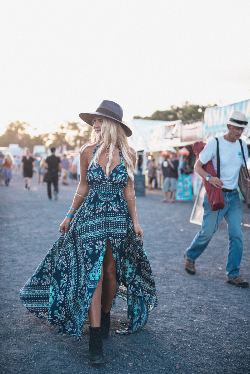 A blonde woman at a music festival, wearing a floppy hat and split maxi dress with turquoise patterns and matching jewelry