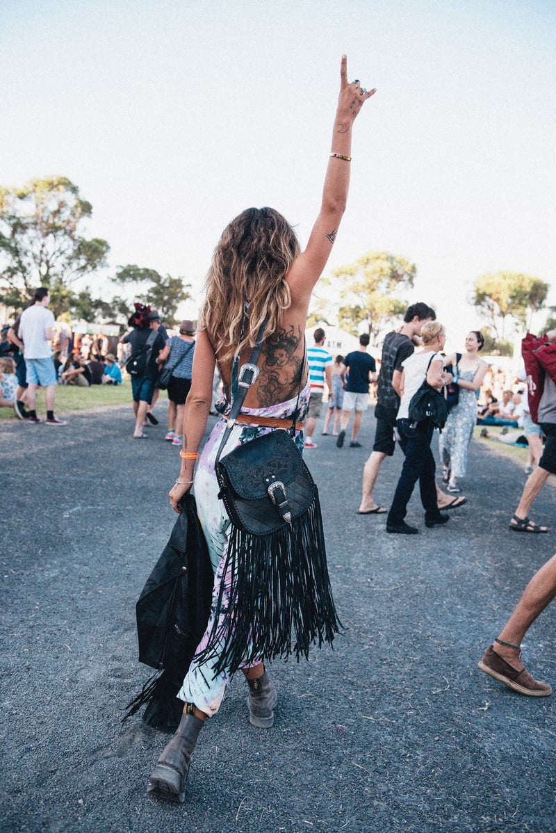 A tattooed woman at a festival wearing a tassled messenger bag and matching boho outfit