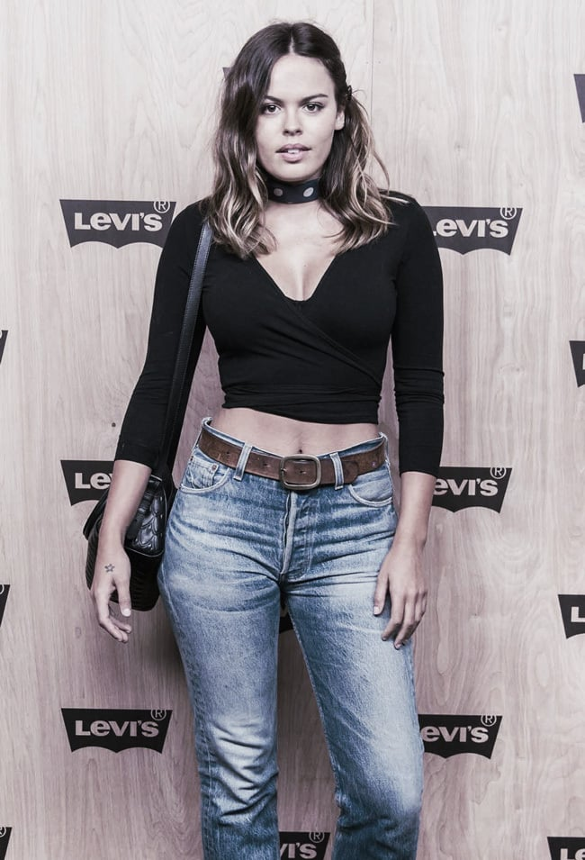 Atlanta de Cadenet wears jeans and a black mock wrap top