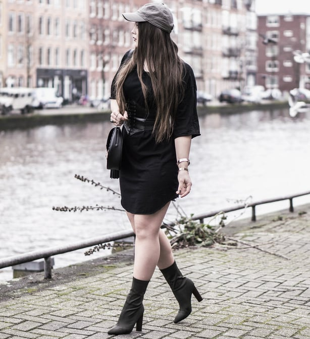 Sonvas wears a black t-shirt dress with a corset belt, heels and a baseball cap
