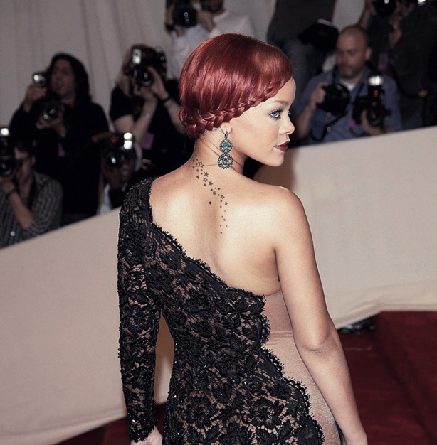 Rhianna displays a back of the shoulder tattoo with elegance.