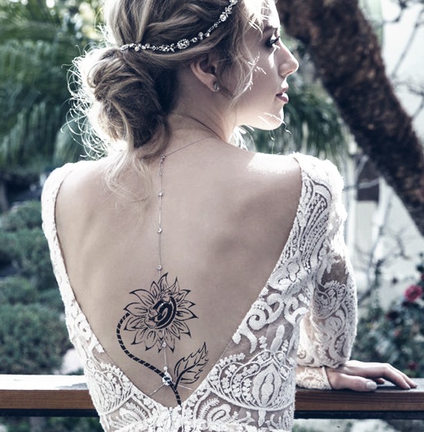 A backless lace dress is an elegant option to show off back tattoos for formal events