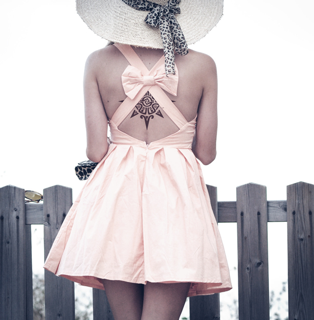 Draw attention to back tattoos with a sweet bow backed dress.