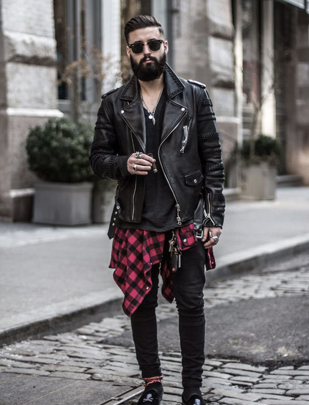 A picture of a streetwear model wearing an urban outfit with a black leather jacket, skinny jeans and a red lumberjack shirt