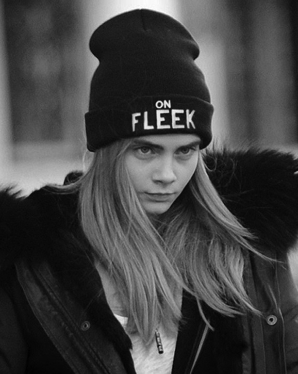 Cara Delevigne wears a black hat with the millenial phrase 'on fleek' written on the front