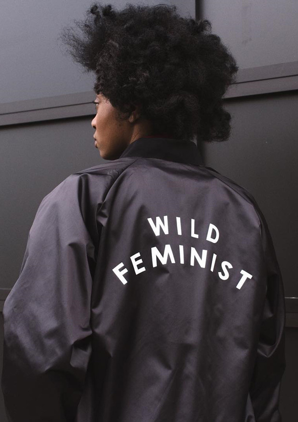 "A woman wears a black bomber jacket with the slogan ""Wild Feminist"" written on the back"